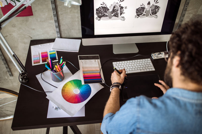 man sitting at desk with monitor, cup of pens, and color wheels while working on graphic design with stylus pad