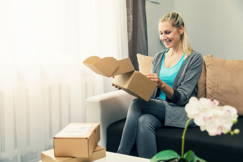woman-smiling-and-sitting-on-couch-while-opening-cardboard-box-package