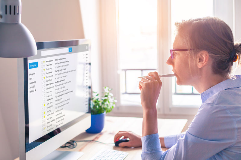 woman-wearing-glasses-and-blue-shirt-holding-pencil-to-mouth-while-using-internet-at-desktop-monitor