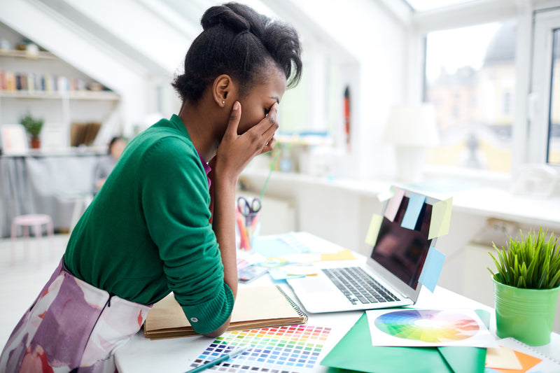 woman-with-hands-on-face-looking-stressed-at-graphic-design-workspace