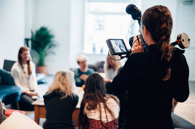 female-videographer-holding-professional-camera-on-shoulder-while-filming-group-of-people-seated-on-floor-around-coffee-table
