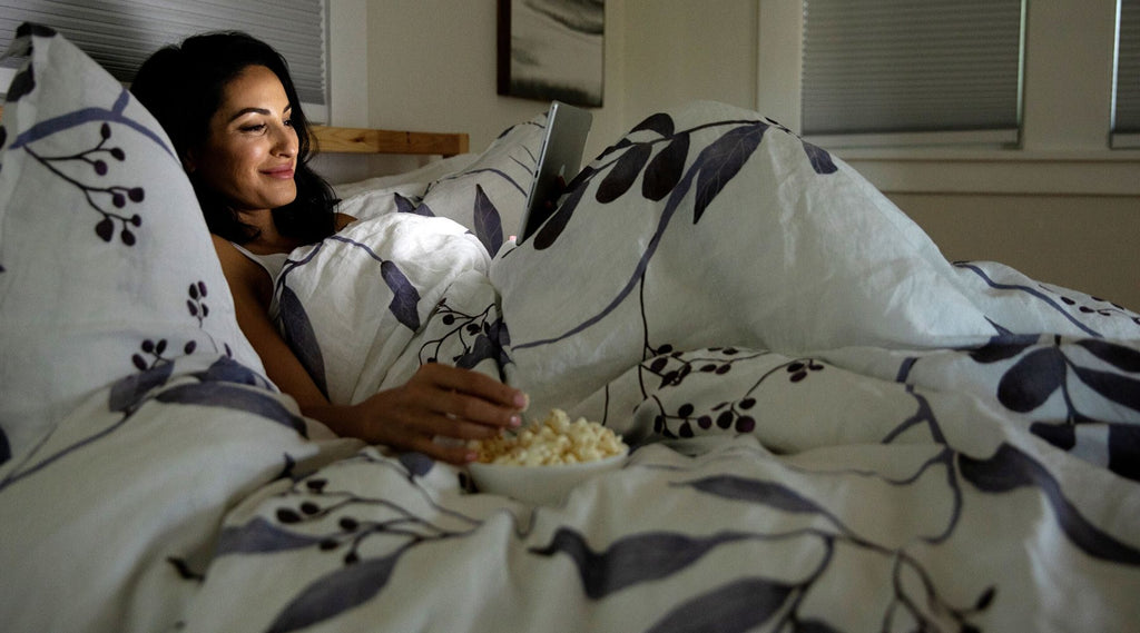 Woman enjoying a movie on her iPad in bed while eating popcorn