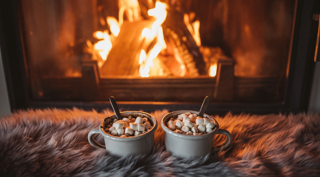 Two cups of hot chocolate on cozy fur in front of fireplace