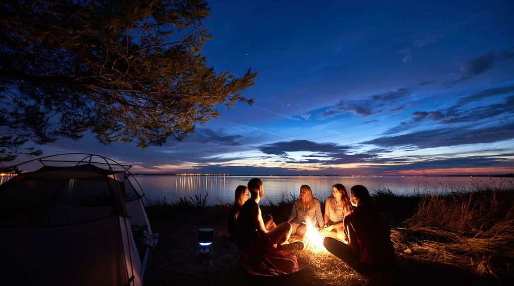 Night summer camping on shore. Group of friends around campfire near tent under evening sky