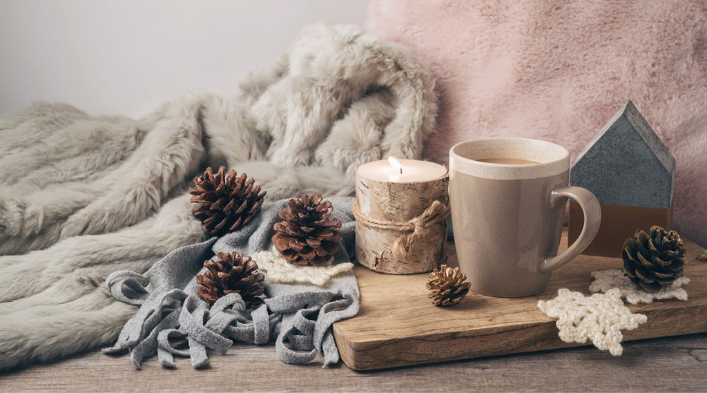 Hygge items including candle cup of coffee pine cones cutting board and cozy throw