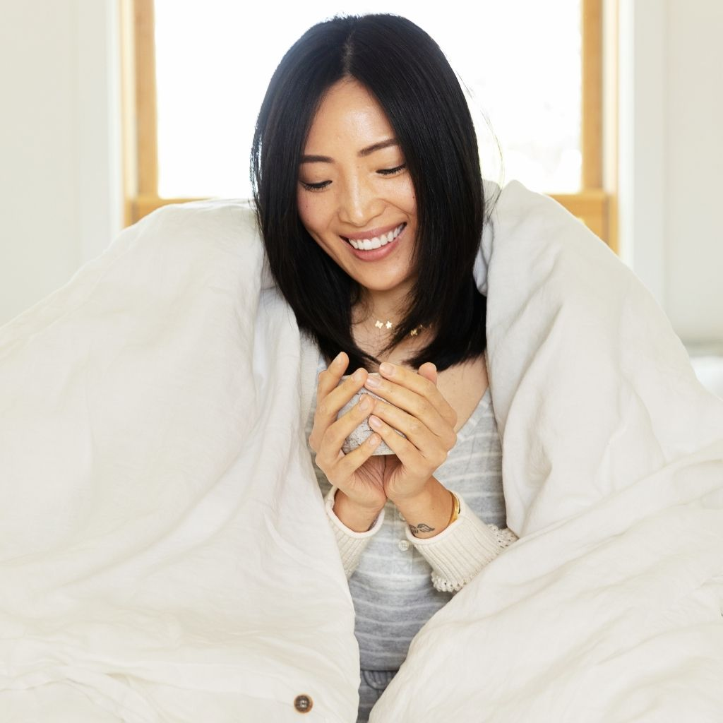 Woman enjoying a warm cup of tea in soft linen bedding from The Modern Dane