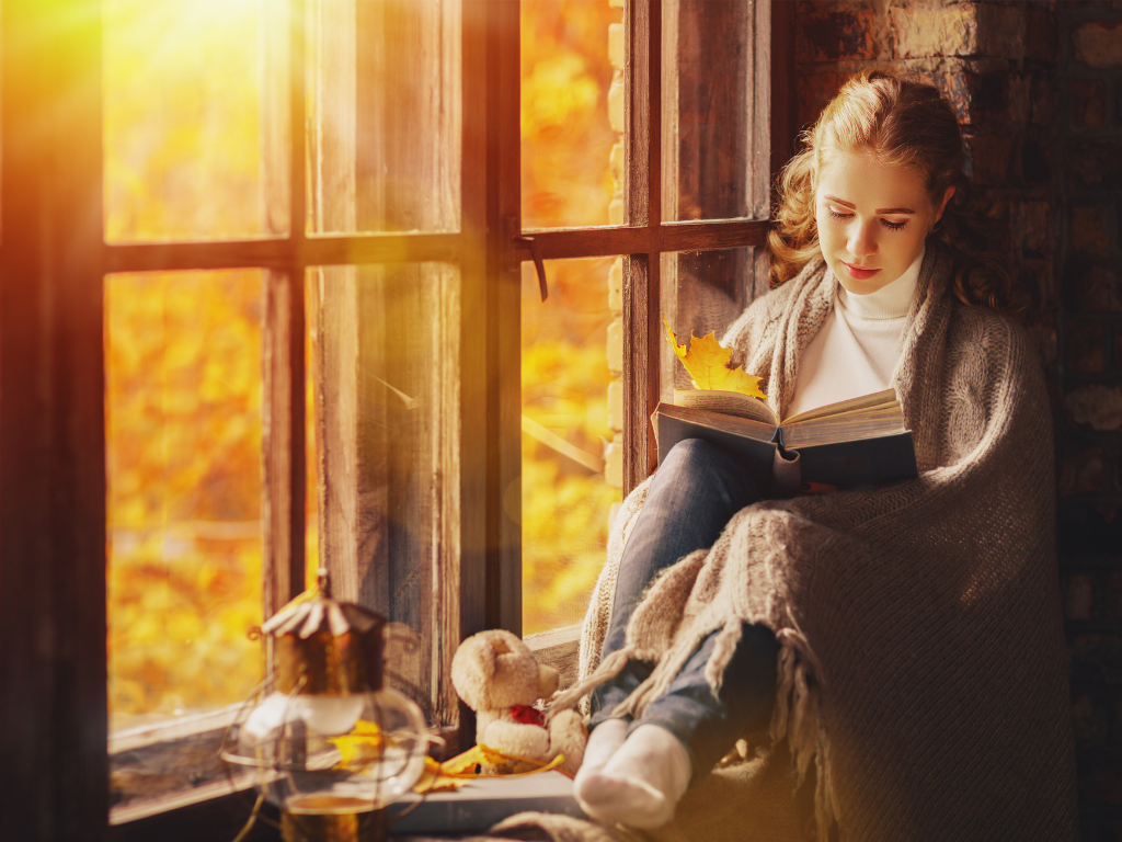 Young woman reading a book in a cozy window nook on a beautiful fall day