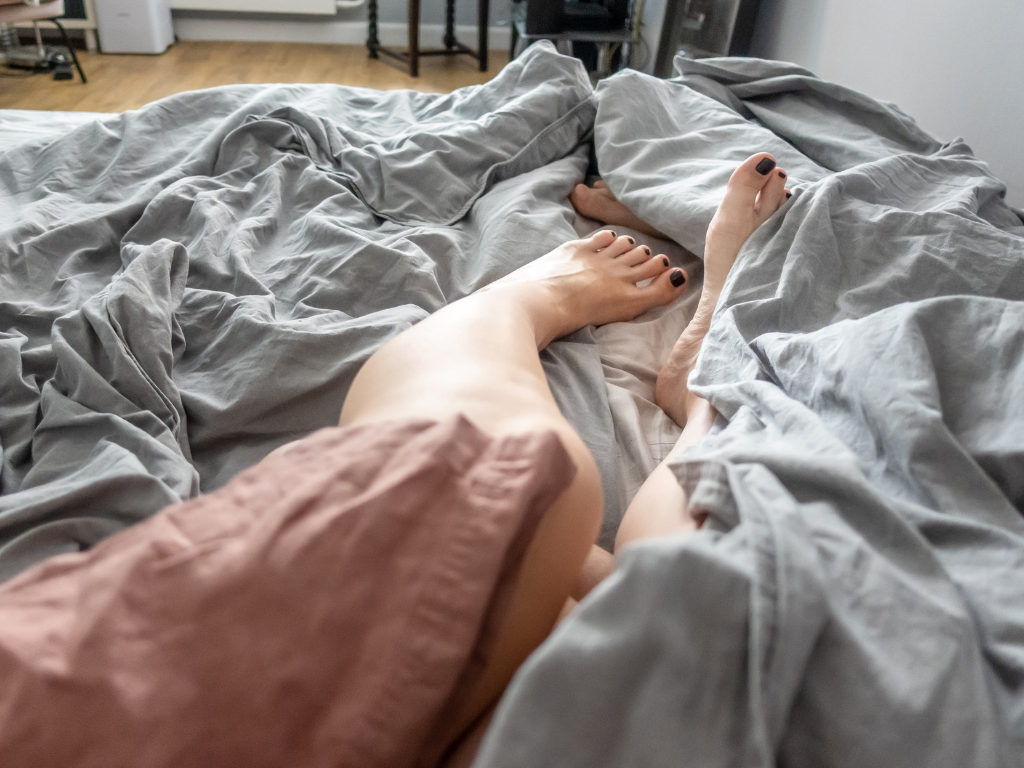 Woman in bed kicking her legs out from under her duvet