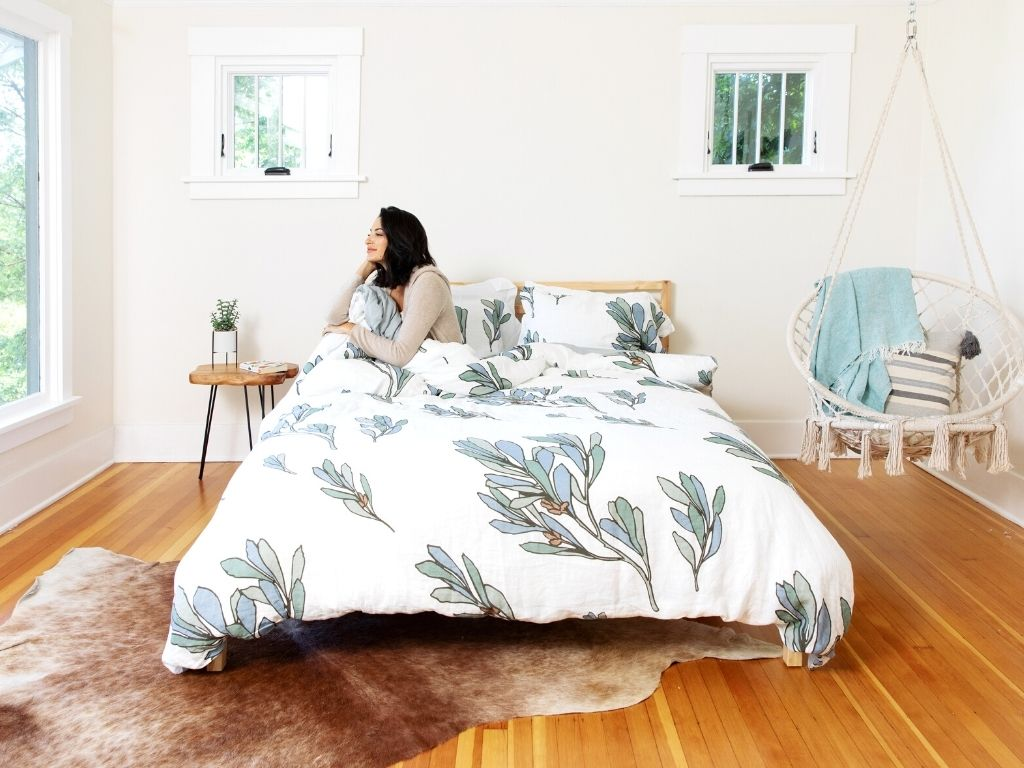 Woman looking out the window in Scandinavian style bedroom with a bed made up with an organic European linen duvet cover with a modern botanical print