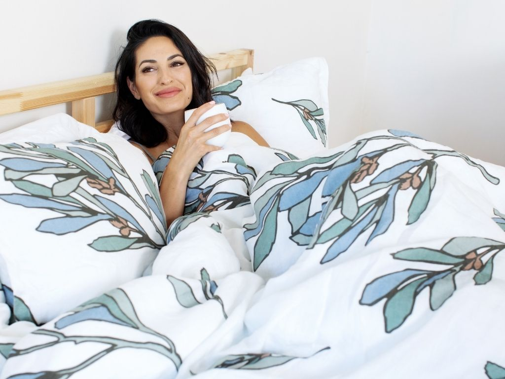 Lady relaxing with a cup of coffee in bed with organic European linen duvet cover with modern Scandinavian design