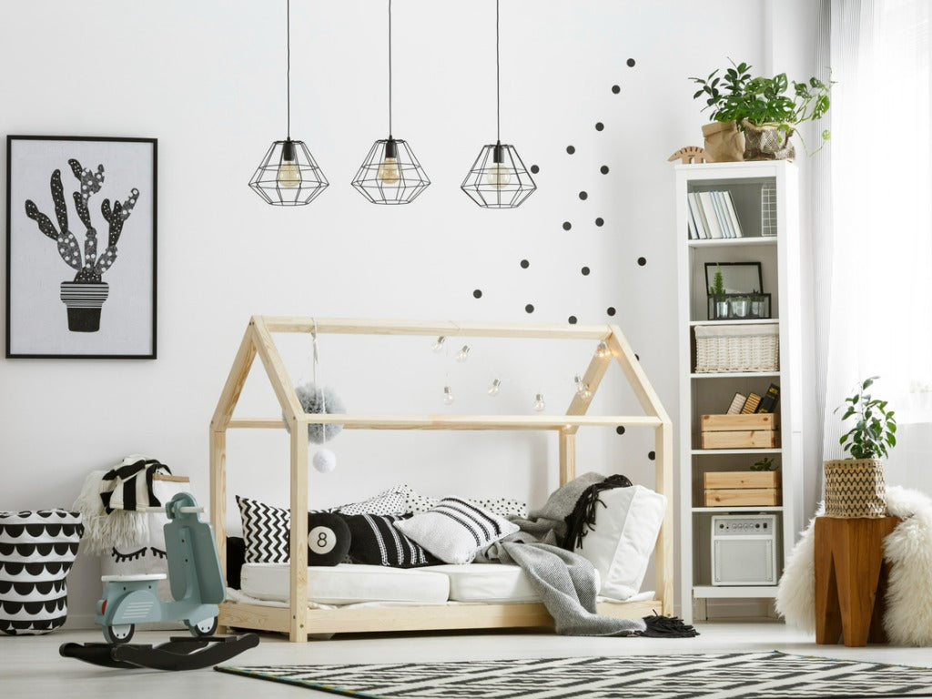 Cozy wooden baby bed in shape of little house with pillows