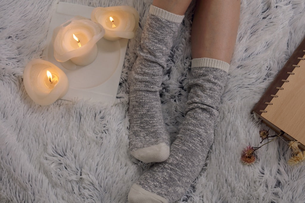 Cozy winter evening , warm woolen socks, soft blanket, candles. Woman relaxing at home, reading a book. Comfy lifestyle