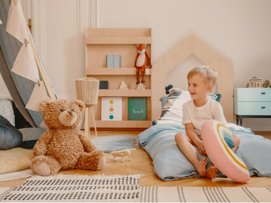 Cute child sitting on a bed in scandinavian kid's play room with toys, tent and wooden furniture
