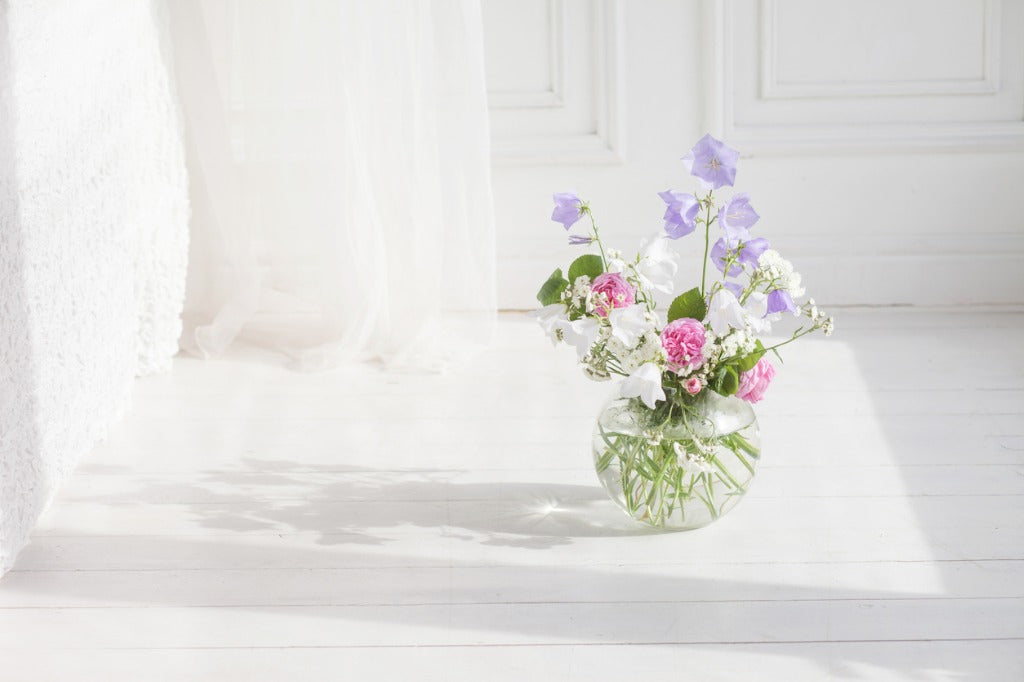 Glass vase with lilac, rose and white floweers in light cozy bedroom interior. White wall, bed with white linen, light blanket or plaid and pillows
