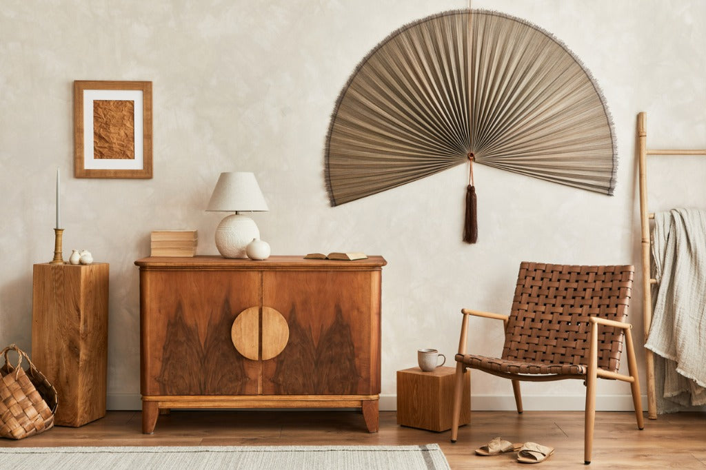 Interior design of Japandi style living room with stylish retro commode, mock up poster frame, cube, table lamp, decoration and elegant personal accessories in home deco