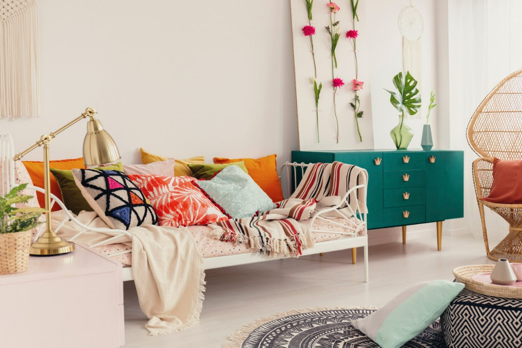 Patterned and colorful pillows on single metal bed in stylish girl's bedroom interior with peacock chair and green cabinet with crown shape handles