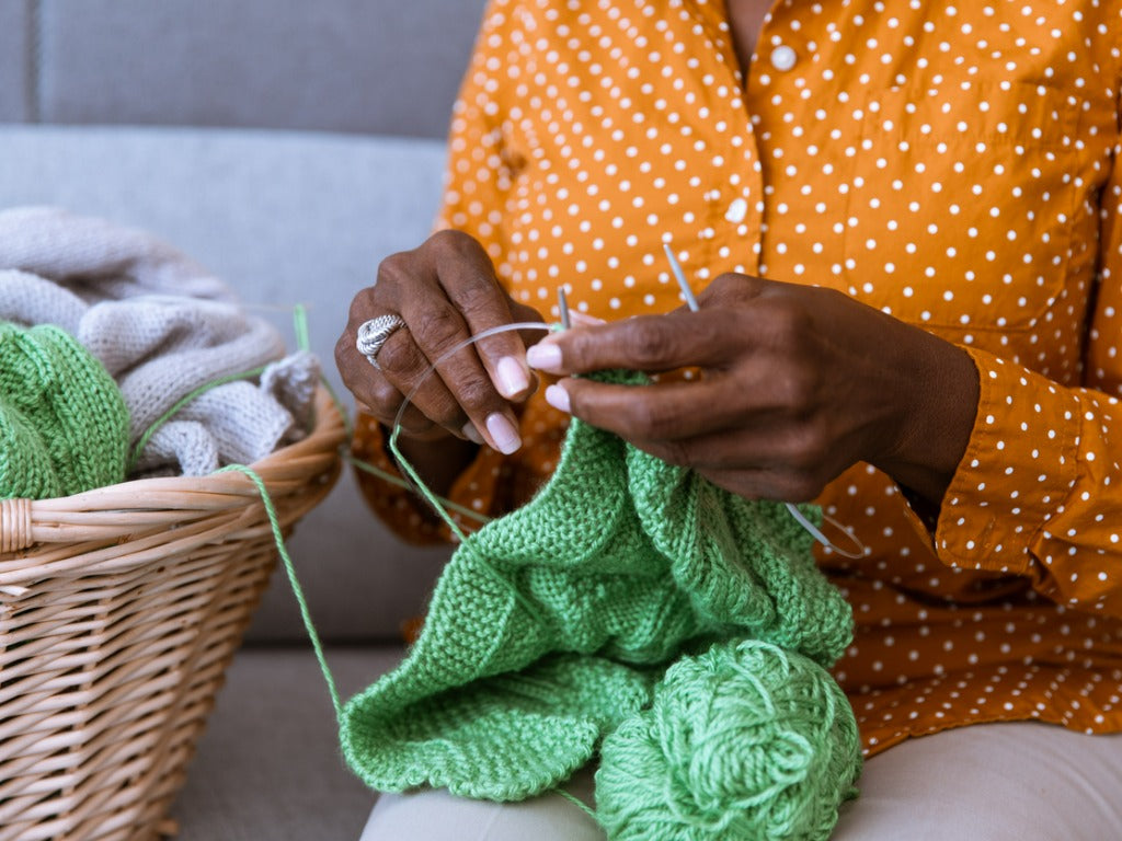 African American woman sitting on the couch and knitting at home