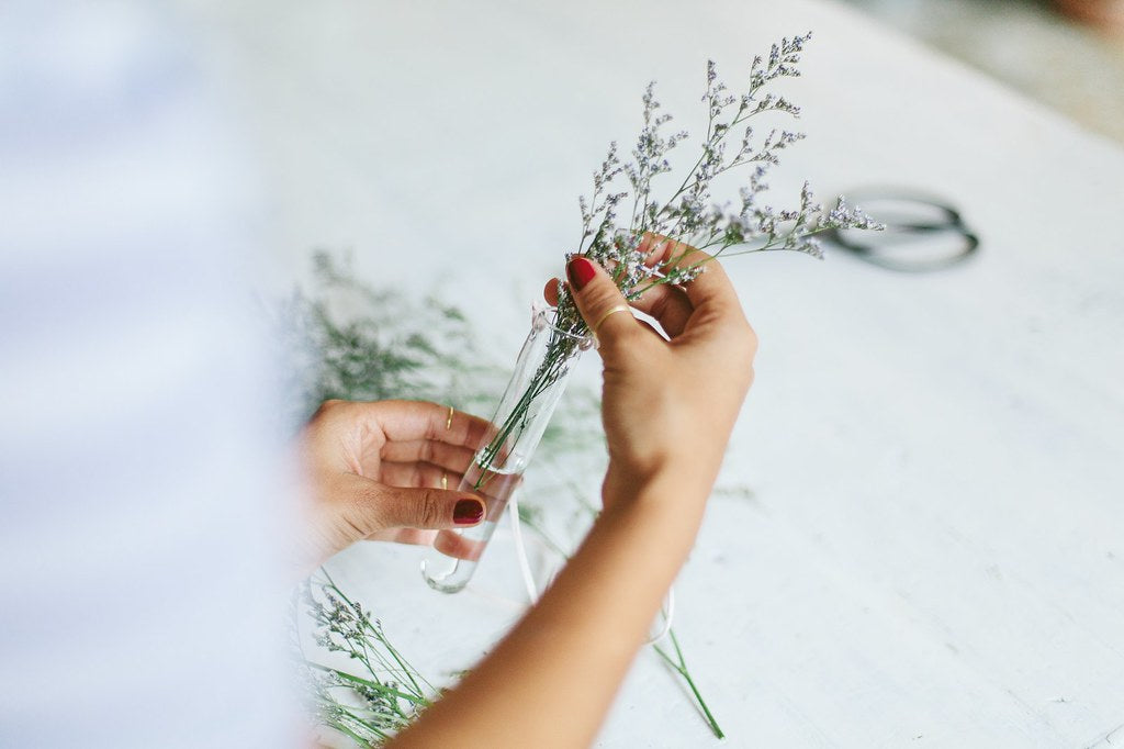 Woman arranging plant nursery in test tubes for beautiful display