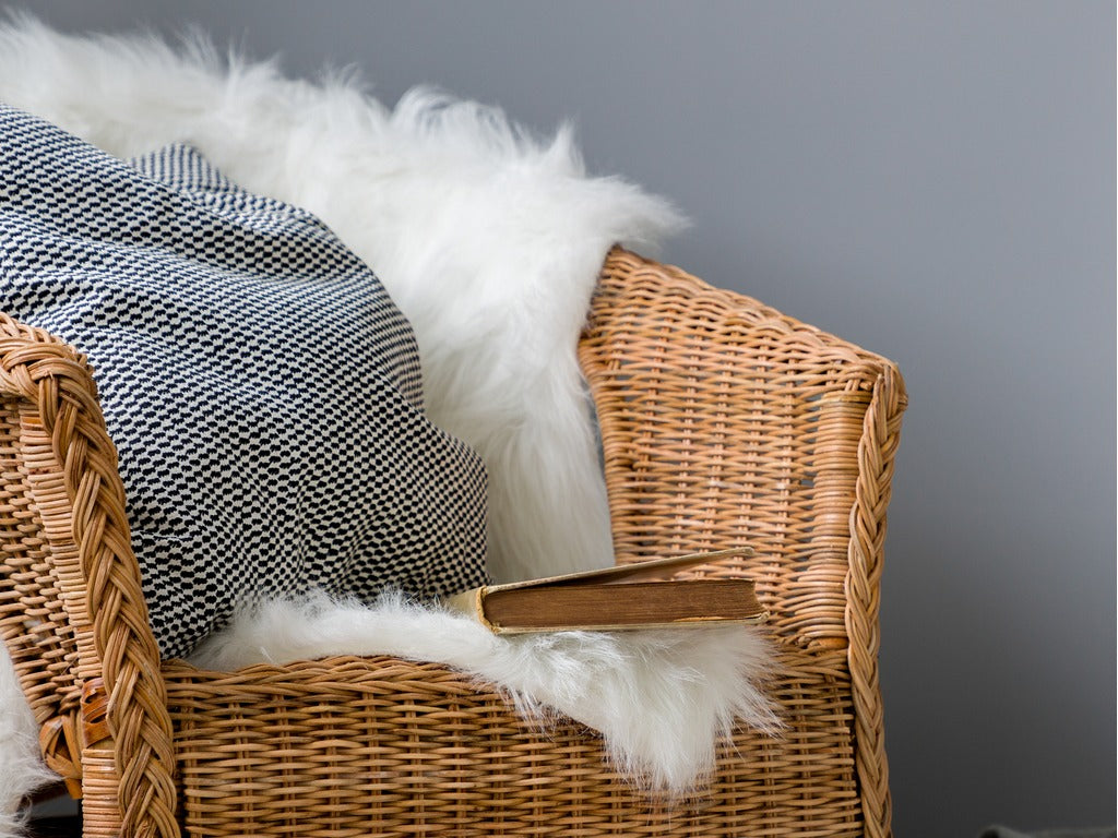 Comfortable, wicker chair with fluffy blanket and pillow, standing in interior with gray wall
