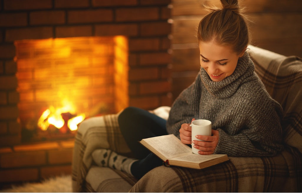 Young woman reading a book by the fireplace on a winter evening