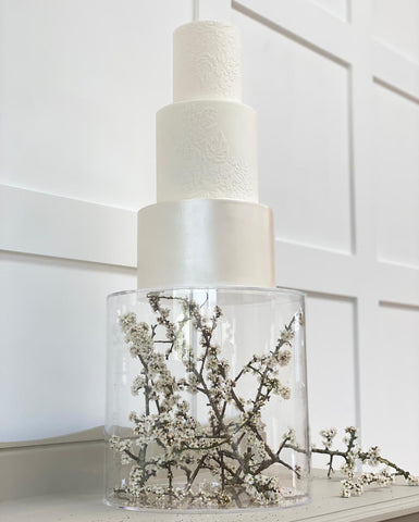 Floating cake stand using fillable acrylic cake tier containing whit flowers