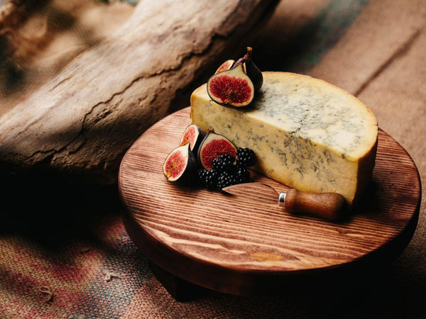 Dark wooden cheese board with blue cheese and fruit