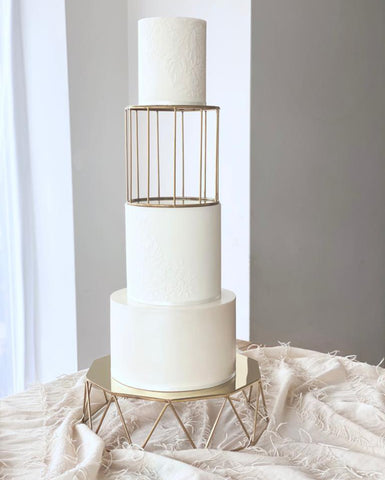 three tiered white wedding cake with gold cake stand and bird cage cake separator.