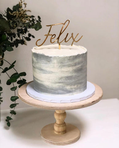 birthday cake on natural wooden cake stand