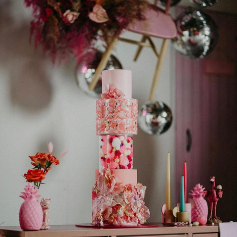 colourful pink multi-tiered wedding cake display using acrylic fillable tier separators