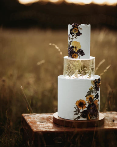 wedding cake on wooden cake board using decorated clear fillable tier