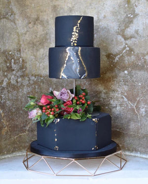 Dramatic black cake using Prop Options separator with central bar on gold cake stand