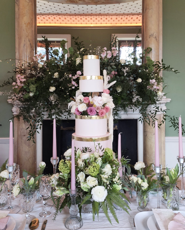 Wedding table display with Gravity defying cake separator with central bar supporting white  wedding cake with roses