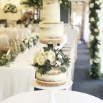 Illusion cake separator with central bar white floral wedding cake