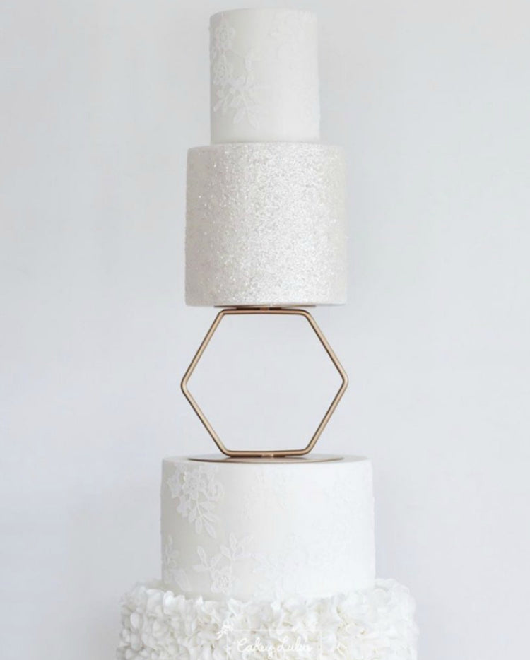Prop Options gold hexagon cake separator supporting white wedding cake