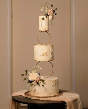Wedding cake display using Prop Options gold hoop tier cake spacer supporting delicate floral wedding cake