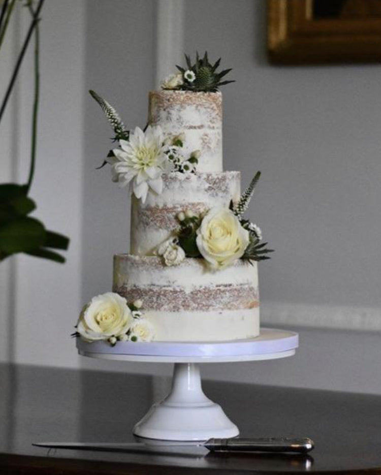 Prop Options Carbon steel adjustable cake stand in white, shortened and displaying beautiful 3 tier nude wedding cake