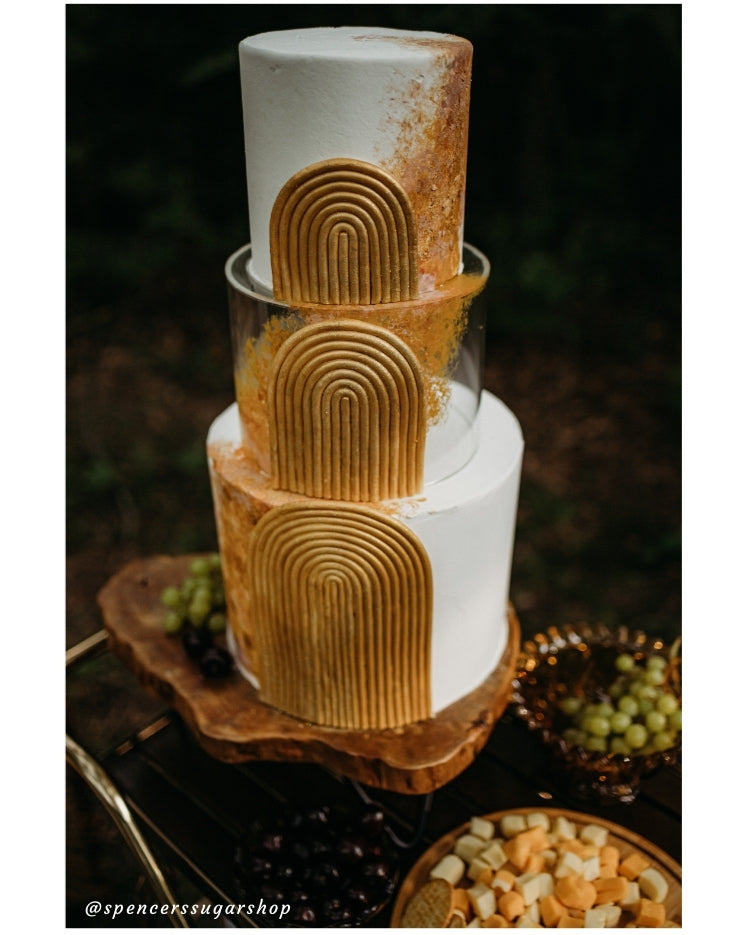 Design by Spencers Sugar Shop - exquisite detailing on gold and white cake in a forest picnic scene using Prop Options' clear tier and log slice stand - close up