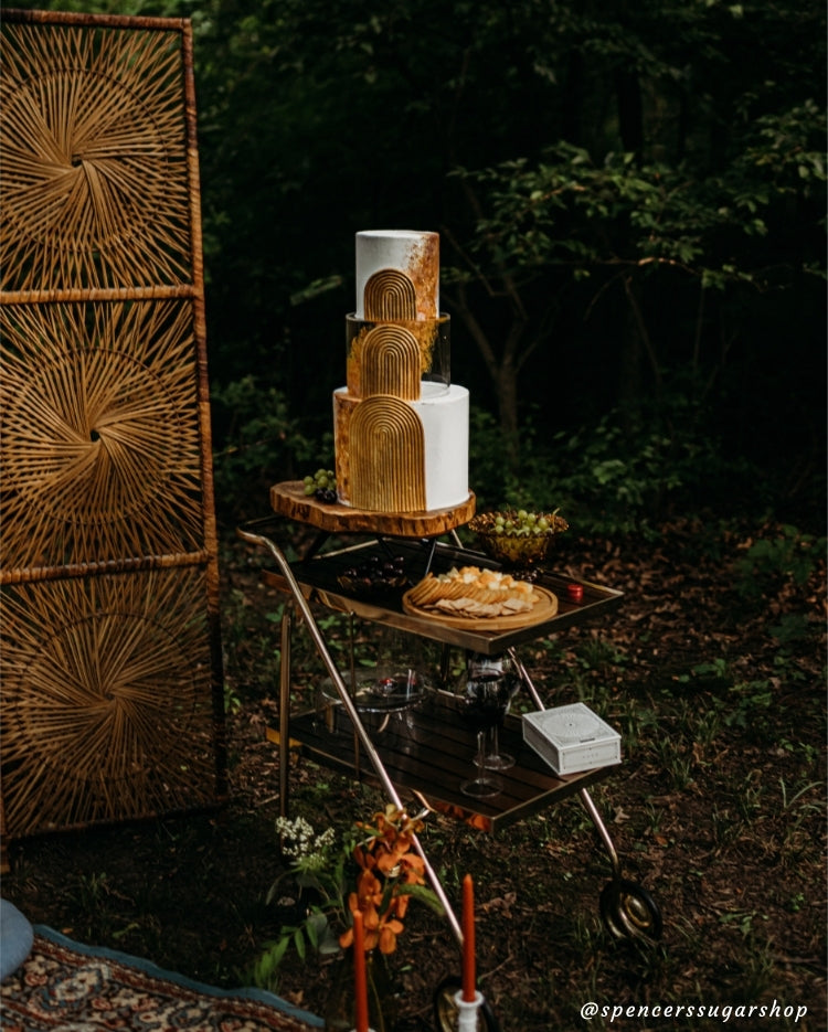 Design by Spencers Sugar Shop - exquisite detailing on gold and white cake in a forest picnic scene using Prop Options' clear tier and log slice stand