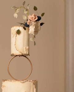 Prop Options gold hoop tier cake spacer supporting delicate floral wedding cake