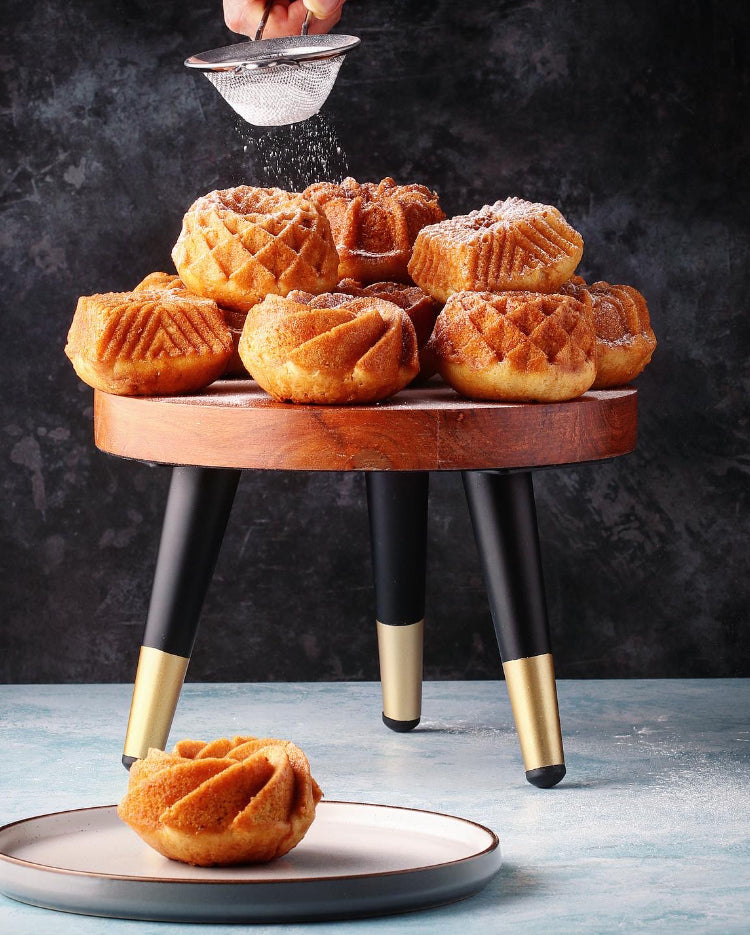 Prop Options Solid wood stand with matte black and gold tapered legs displaying stunning bakes being dressed with icing sugar