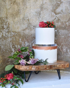 Ultra polished acrylic cake separator supporting cake and florals on solid wood log stand