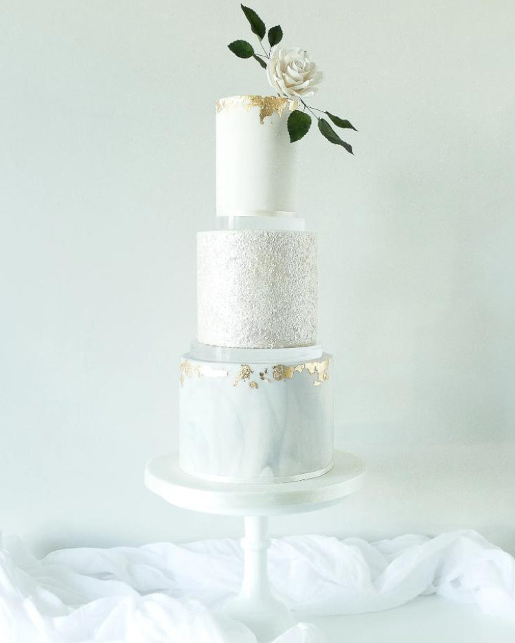 Ultra polished acrylic cake separator supporting stunning white tiered cake with rose
