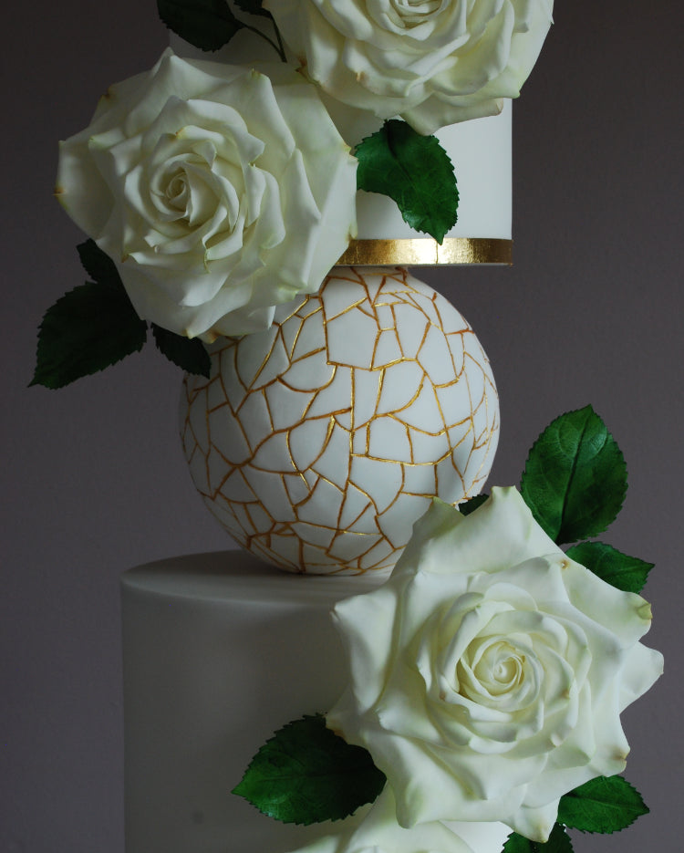 Prop Options Adjustable cake separator with central bar in use expertly decorated with a white and gold design with white roses