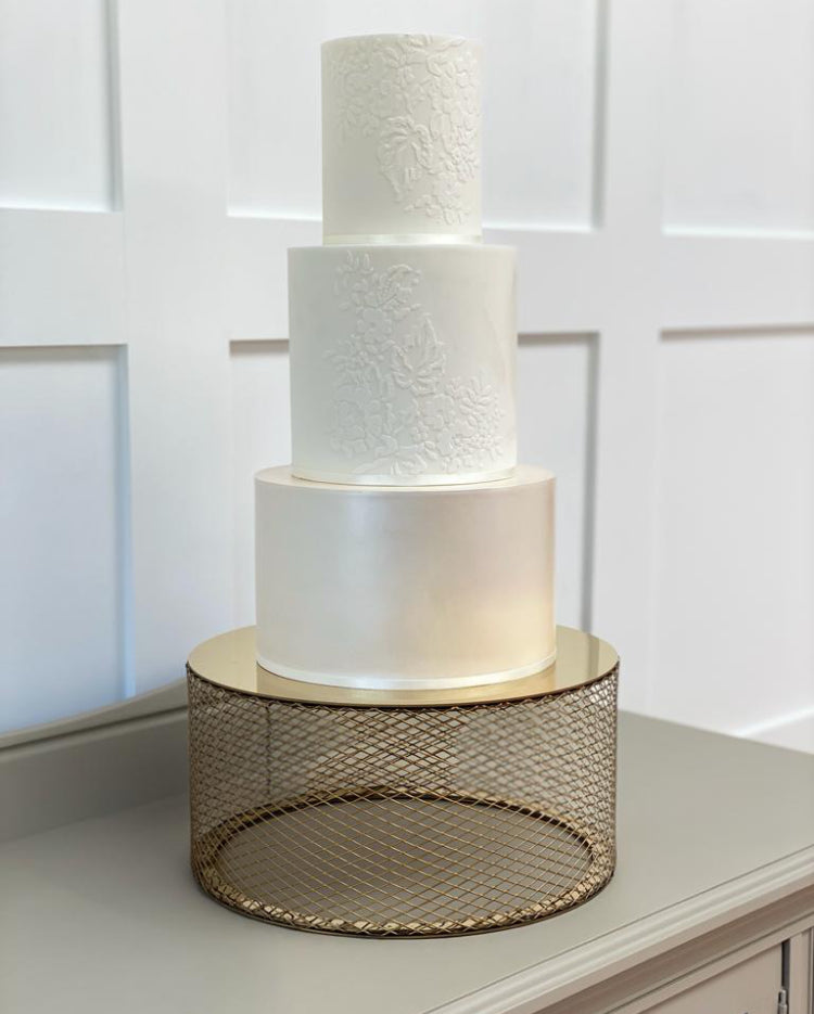 Gold metallic mesh cake stand with tiered wedding cake