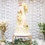 Prop Options Large metallic gold plinth cake stand showcases celebration cake and desserts