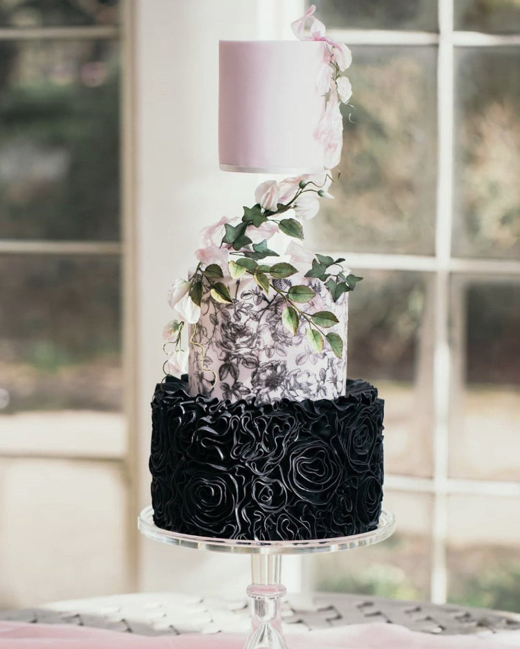 Prop Options Z bar floating tier cake separator used on stunning black and white wedding cake with floral design and foliage