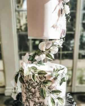 Prop Options Z bar floating tier cake separator used on stunning black and white wedding cake with floral design and foliage in detail