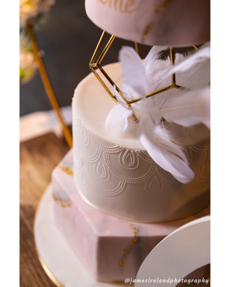 Prop Options Gold Geometric pentagon spacer showcasing beautiful gold decorated tiered cake with intricate detail - close up