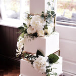 Prop Options gold rectangle cake spacer supporting white wedding cake with floral design and white flowers