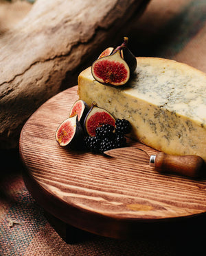 Prop Options Rustic olive wooden round cheese board with cheese and blackberries